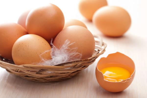 Желток в скорлупе и коричневые яйца в корзине
