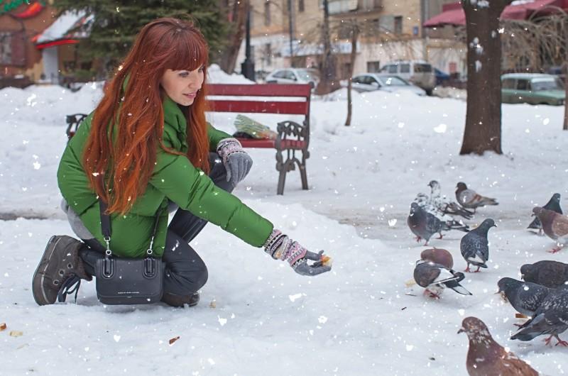 Девушка подкармливает голубей зимой